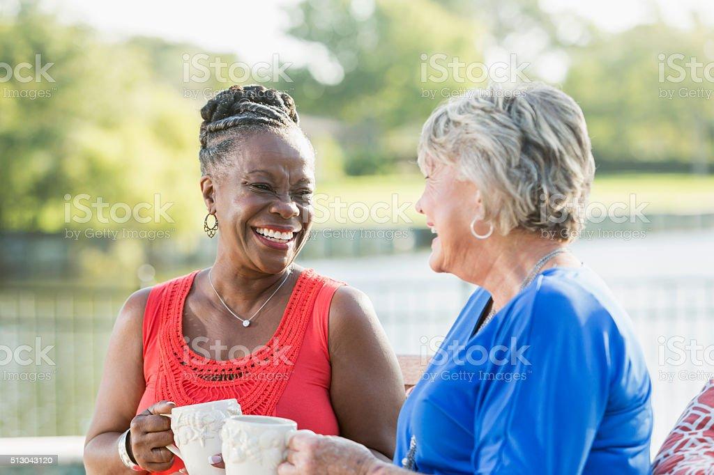 Senior women enjoying cup of coffee in back yard stock photo