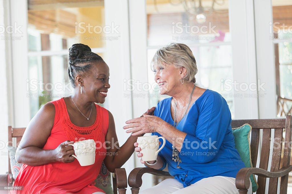 Senior women enjoying cup of coffee together, talking stock photo