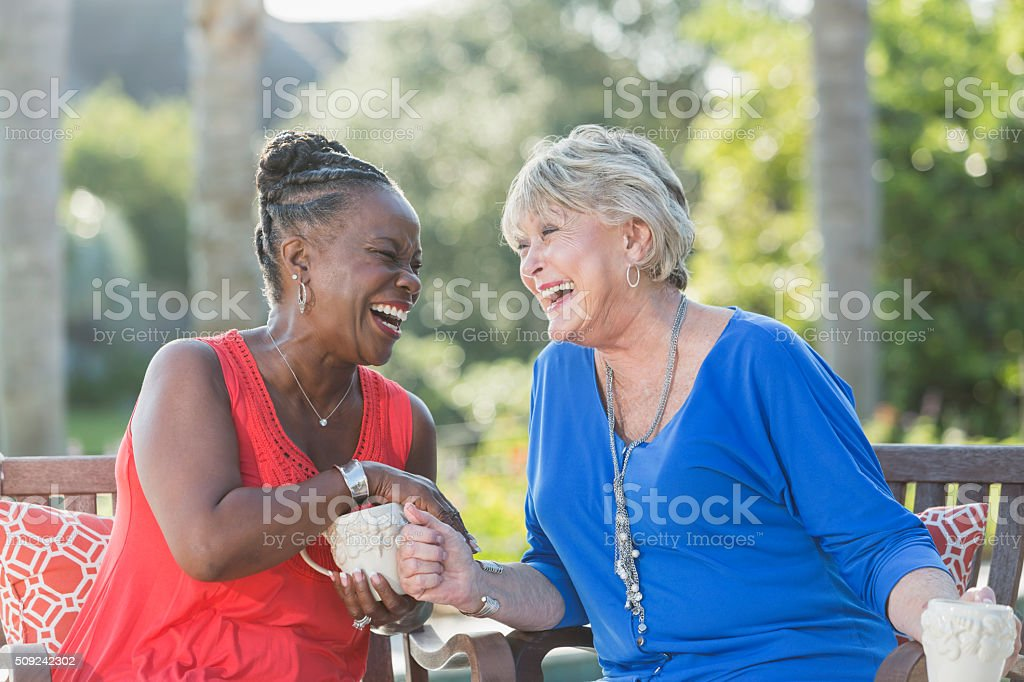 Senior women enjoying cup of coffee together, talking stock photo