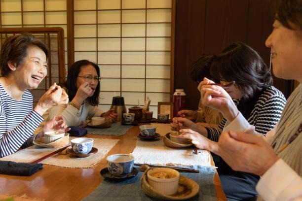 一緒に食事を楽しんで 5 シニア女性 - 談笑する ストックフォトと画像