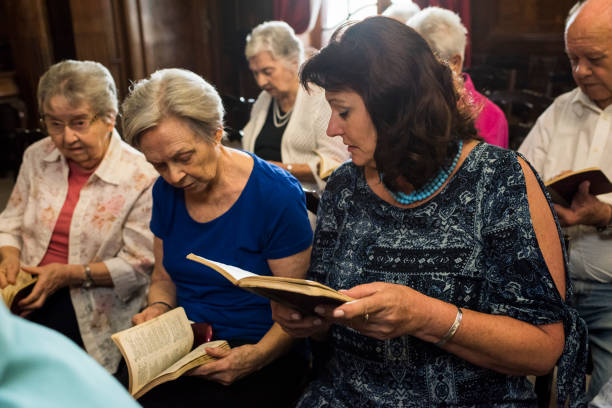 Senior women find page in hymnal to join in the singing stock photo