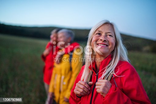 Happy senior women friends on walk outdoors in nature at dusk.
