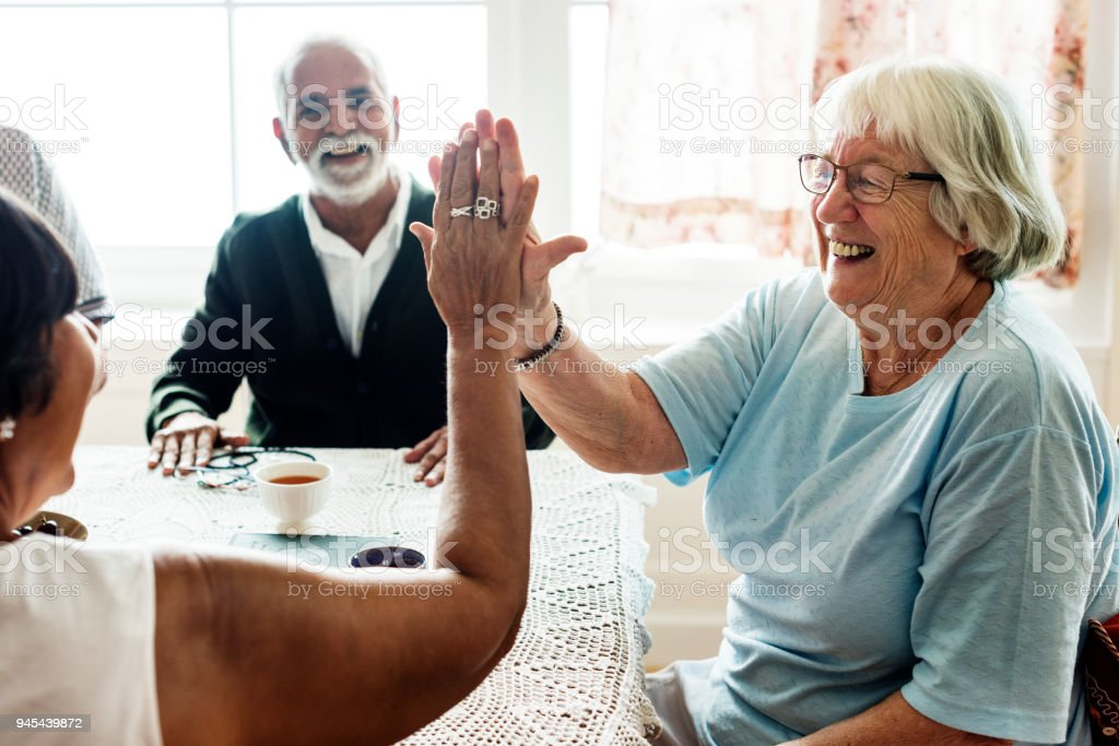 Senior women giving each other high five royalty-free stock photo