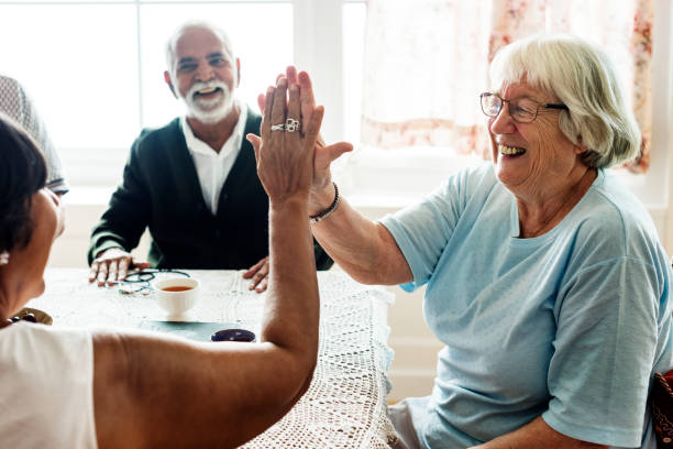 senior women giving each other high five - geriatrics stock pictures, royalty-free photos & images