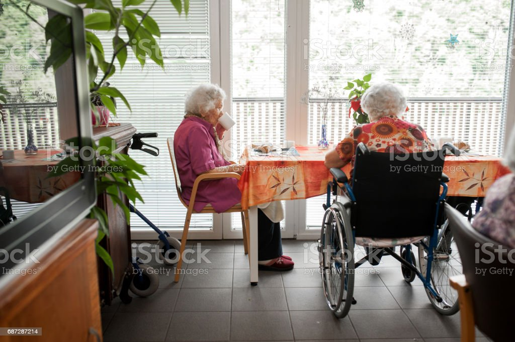 Senior Women Having Breakfast Near The Window In The Retirement Community stock photo