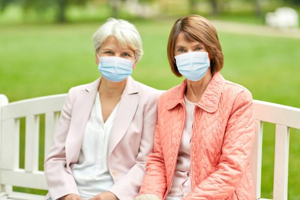 senior women in medical masks at park stock photo