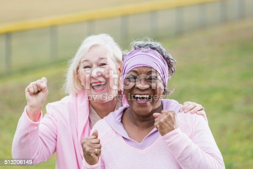 Multi-ethnic senior women (60s) wearing pink clothing, rallying for breast cancer awareness.  Main focus on African American woman.