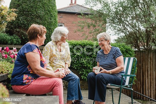 Three senior women are sitting in the garden with a cup of tea while they chat and laugh together.