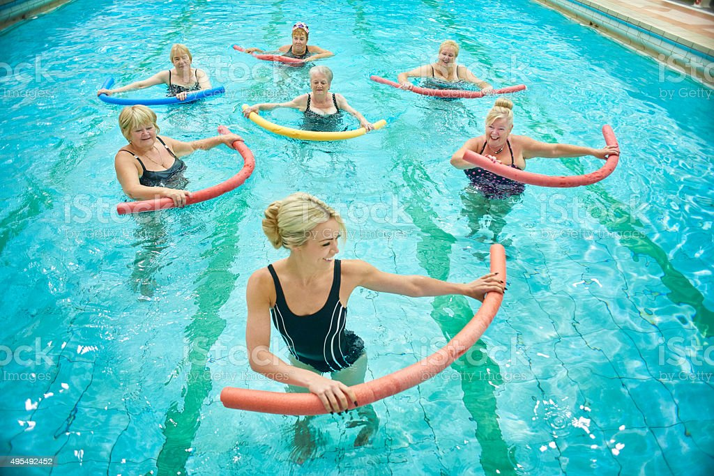 senior donna guidato da istruttore di aerobica in acqua femminile - foto stock