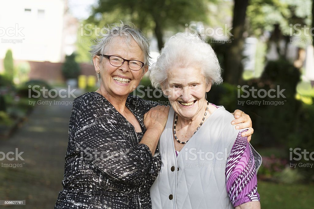 senior women niece embracing old aunt happiness stock photo