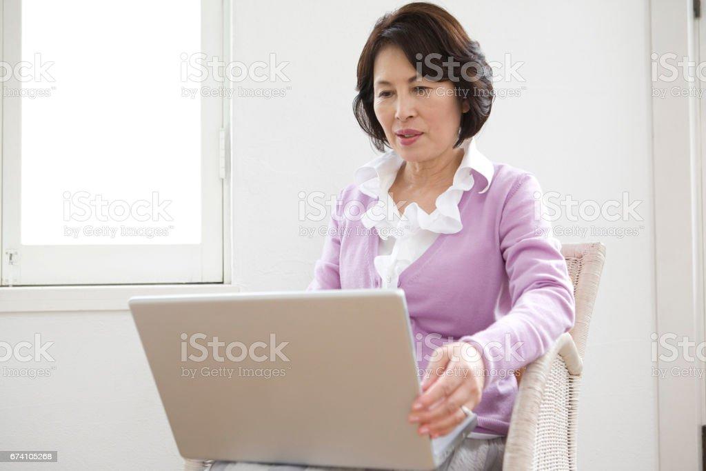 Senior women open the laptop royalty-free stock photo