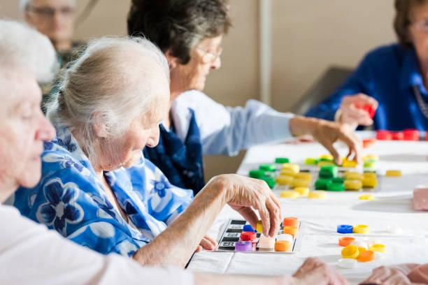 Senior women playing multiple bingo cards stock photo