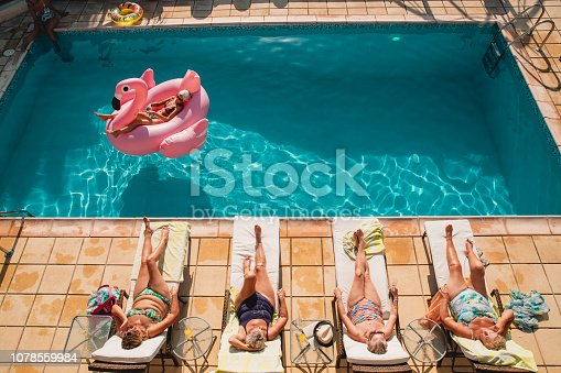 Group of senior women relaxing by the poolside while on holiday. There are four women laid on sun beds and then one woman laid on an inflatable flamingo on the pool water.