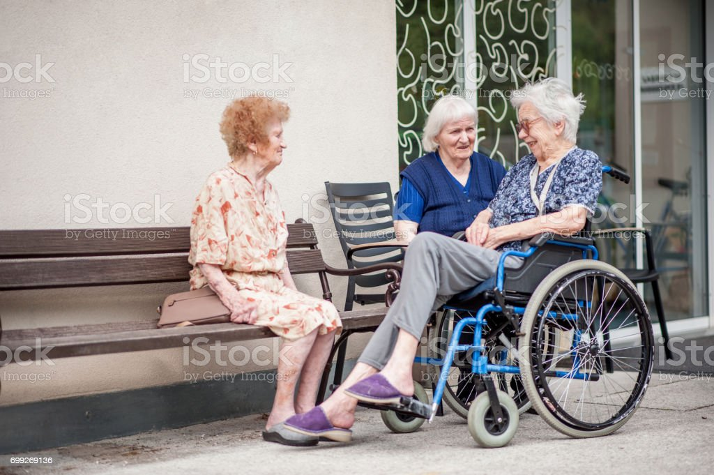 Senior Women Relaxing Outside The Retirement Home stock photo