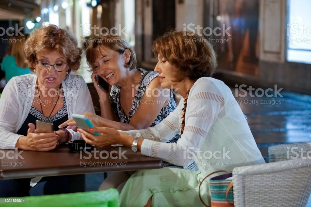 Senior women relaxing with mobile phone in sidewalk cafe stock photo