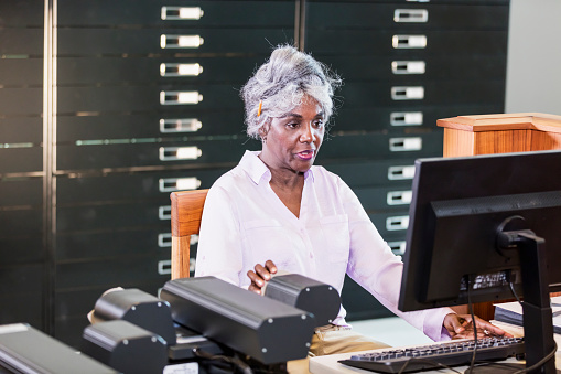 A senior African-American woman in the library, using a computer to review historical documents stored on microfiche.