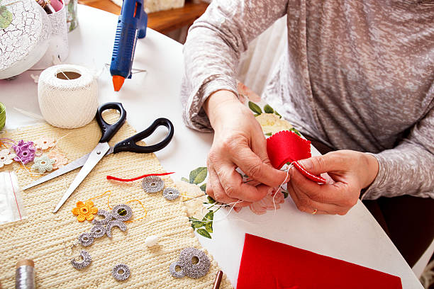Senior women sews by hand stock photo