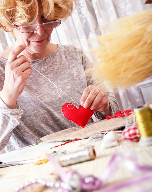 senior damen sews von hand - altes schmuckkunsthandwerk stock-fotos und bilder