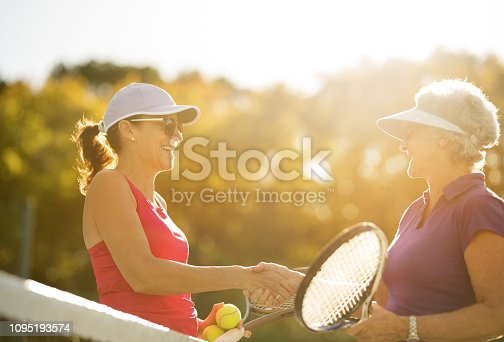 Mature females shaking hands after a match on tennis court.
