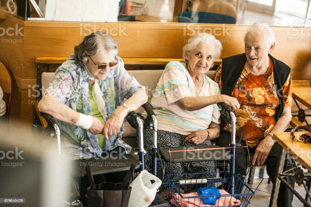 Senior Women Socializing  In The Lobby Of The Retirement Community stock photo