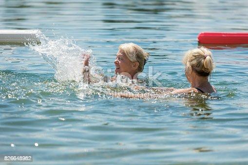 istock Senior women splashing each other while swimming 826648982
