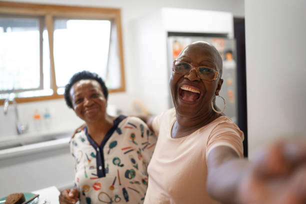 Senior women taking a selfie in the kitchen Senior women taking a selfie in the kitchen baby boomers stock pictures, royalty-free photos & images