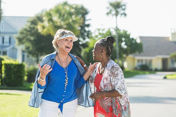 senior donna facendo una passeggiata in una giornata di sole, parlando - vicino foto e immagini stock