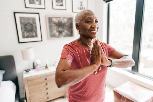Senior women taking care of her wellbeing, she is exercising at home in sportswear stock photo