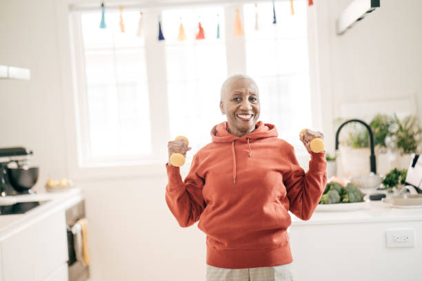 Senior women taking care of herself  she exercise with  dumbbells at home stock photo