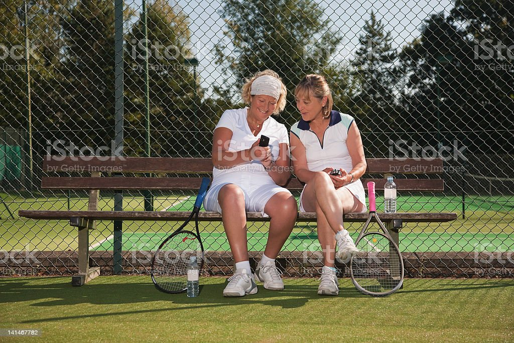 Senior women texting on tennis court stock photo