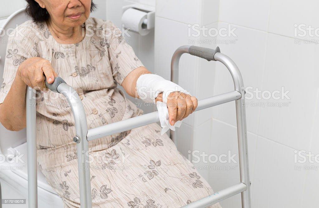 Senior women using the toilet with walker. stock photo