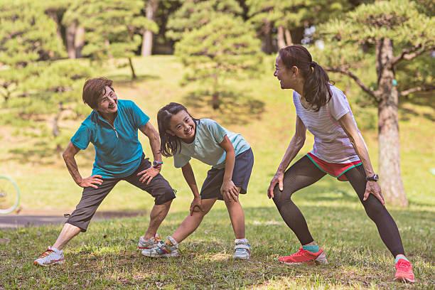 Senior women with litlle girl stretching in Yoyogi park stock photo