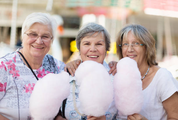 senior women with pink cotton candy stock photo