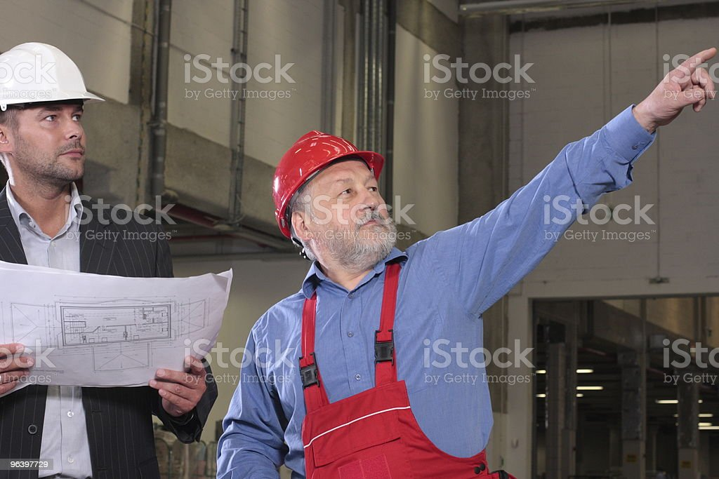 senior worker and engineer with a set of blueprints - Royalty-free 55-59 Years Stock Photo
