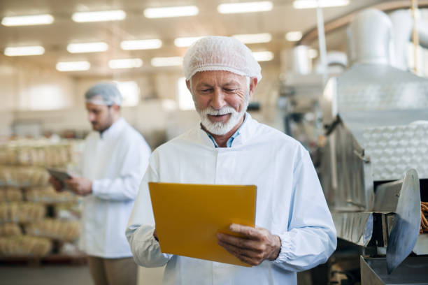 Senior worker checking documentation while standing in food factory. Protective uniform on. Senior worker checking documentation while standing in food factory. Protective uniform on. food warehouse stock pictures, royalty-free photos & images