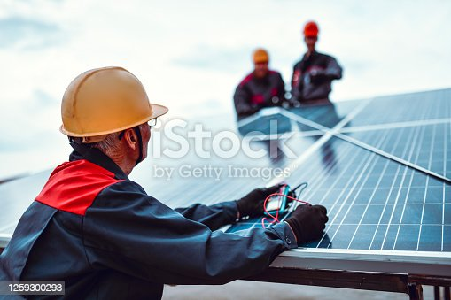 Senior Worker Checking Impedance While Younger Ones Measure Solar Panel