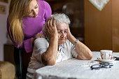 istock Senior worker consoling her elderly patient 1272458986