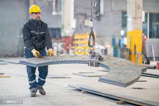 Senior worker holding and working with remote control for operating crane