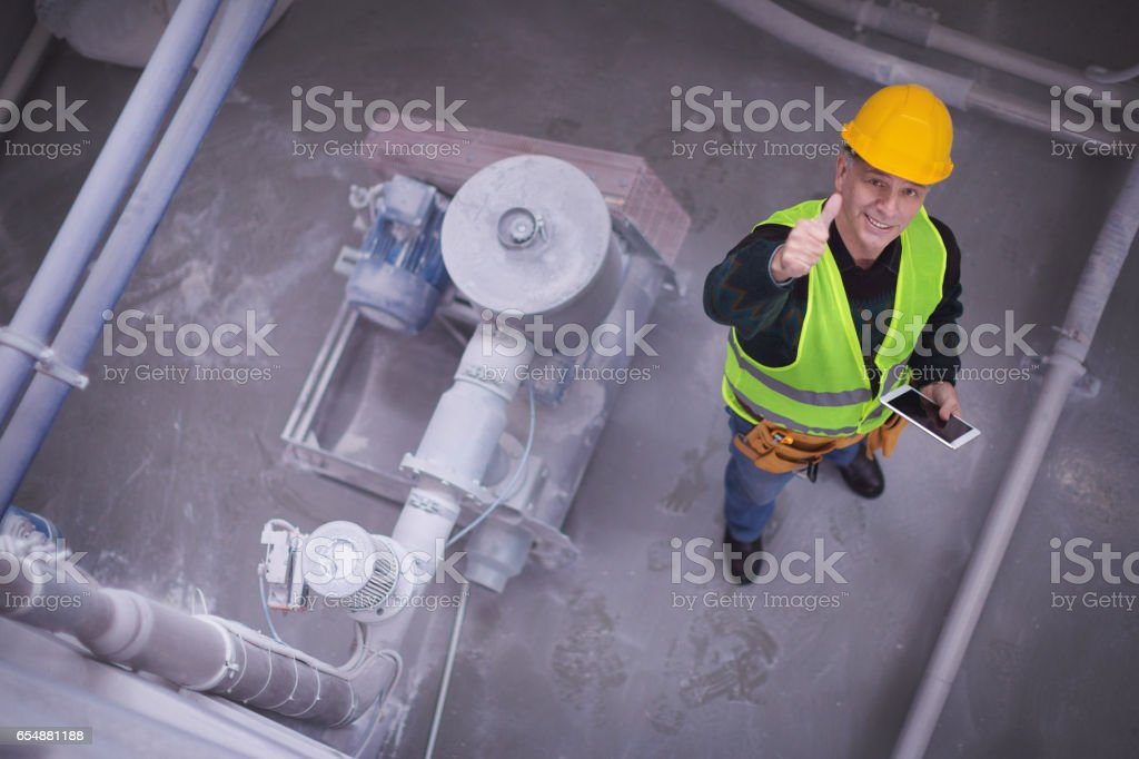 Senior worker in factory showing thumbs up high angle shot stock photo