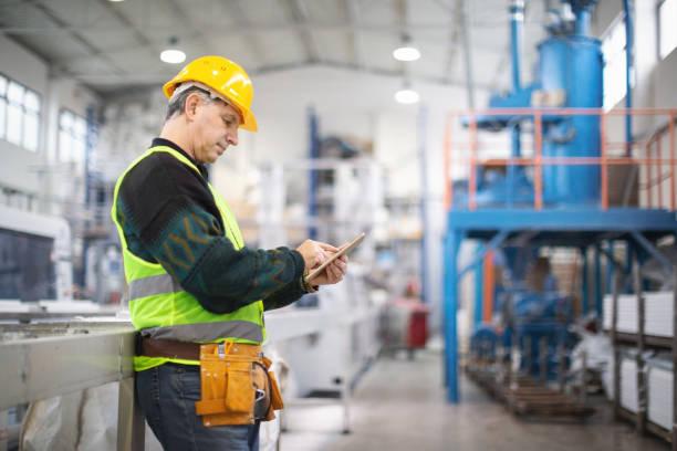 senior werknemer in de fabriek die machines - kwaliteitscontroleur stockfoto's en -beelden