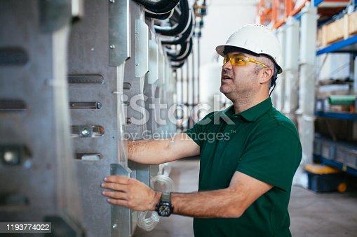 941796726 istock photo Senior worker in the factory operating machines stock photo 1193774022