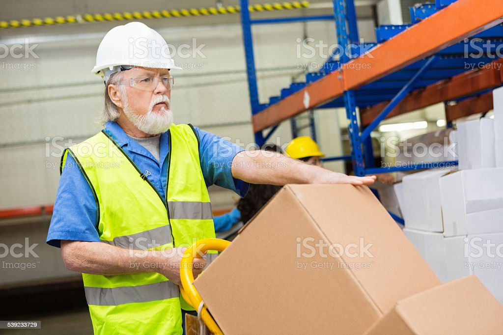 Senior worker in warehouse using dolly to move boxes royalty-free stock photo