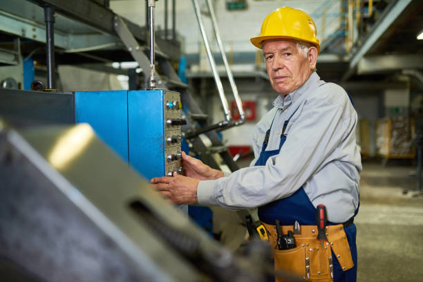 Senior Worker Operating Machine Units at Factory stock photo