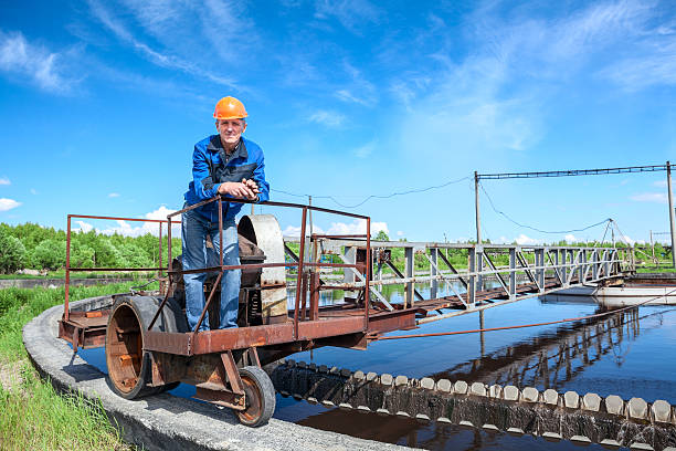 Senior worker standing on waste water treatment unit Senior worker standing on waste water treatment unit on industrial plant sewage treatment plant stock pictures, royalty-free photos & images