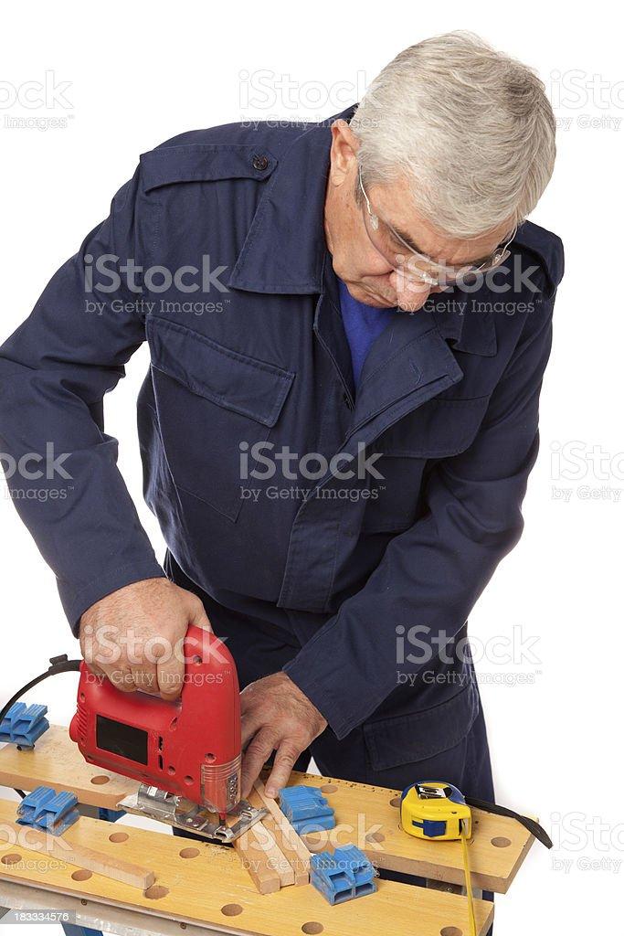 Senior worker (carpenter) using sawing equipment royalty-free stock photo