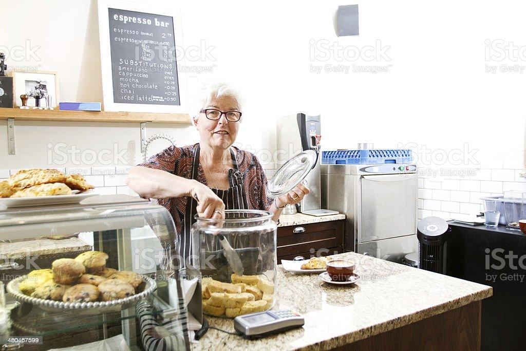 Senior working in coffee shop stock photo