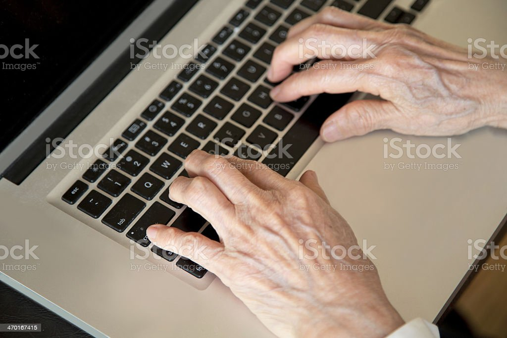 Senior wrinkled hands on laptop typing stock photo
