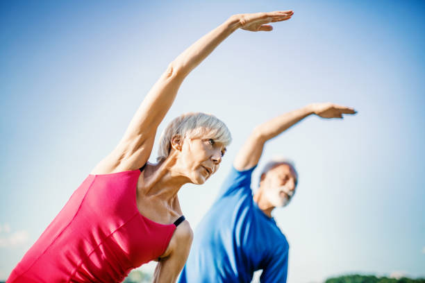 Senior Yoga. Mature couple exercise outdoors. Side view. Horizontal. exercise class stock pictures, royalty-free photos & images