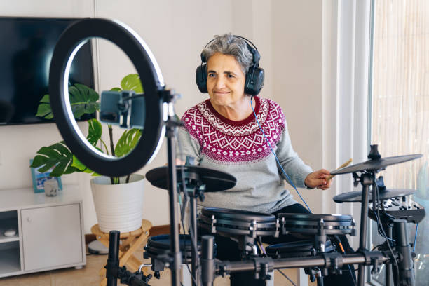 Senior youtuber making another video and playing electronic drum kit At Home stock photo