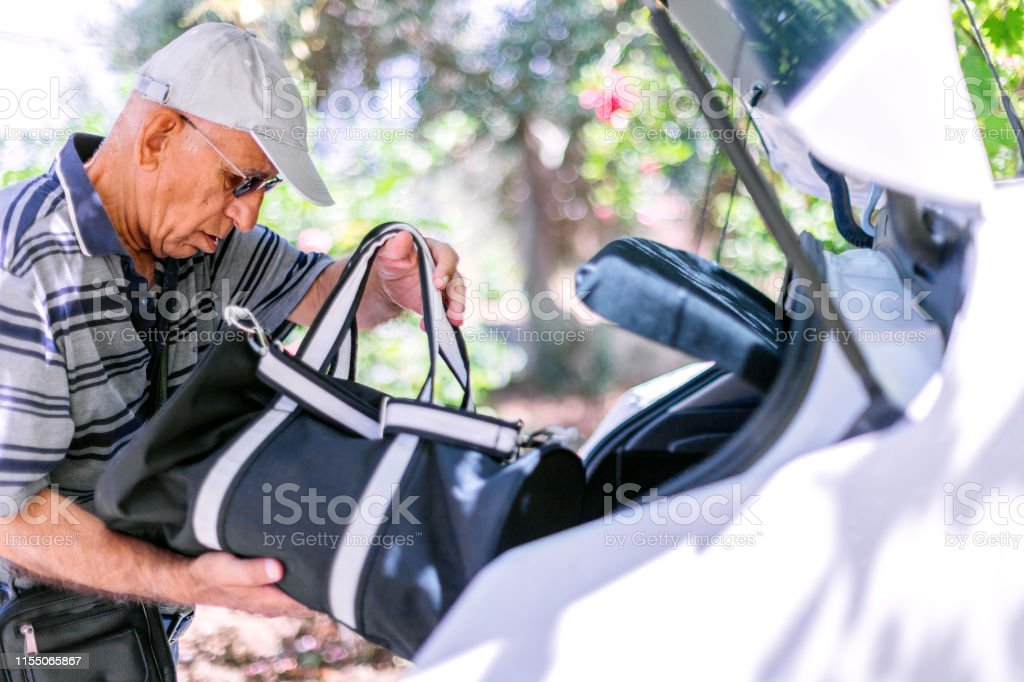 Seniorman packing suitcase in a car for summer holiday